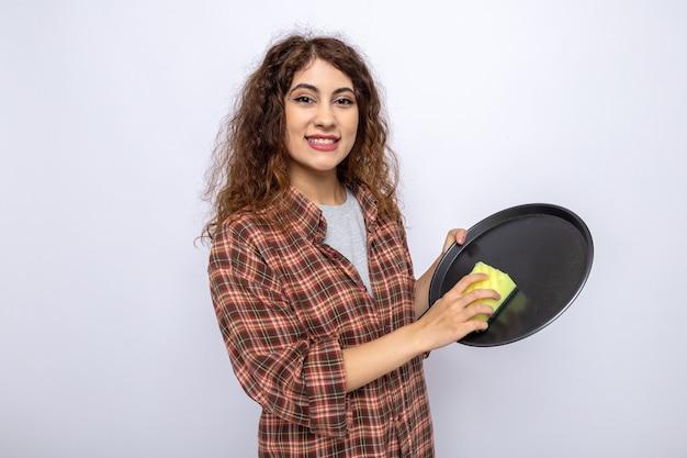 Souriante jeune femme de ménage plateau de lavage avec éponge de nettoyage isolé sur mur blanc