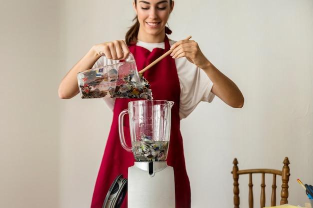 Souriante jeune femme mettant des papiers déchirés dans un mélangeur