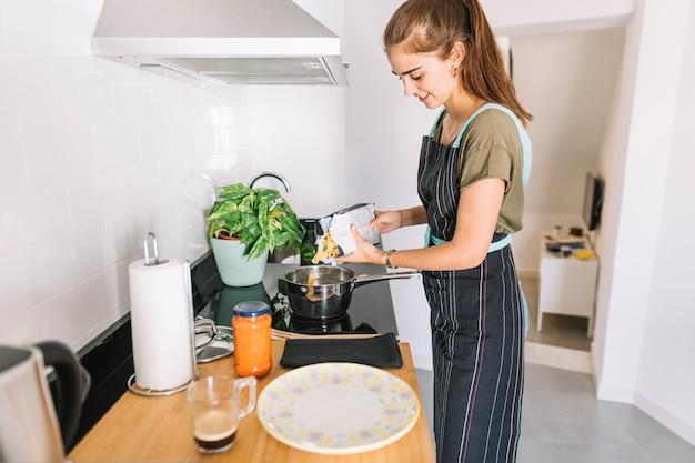 Souriante jeune femme mettant des pâtes dans la casserole sur la cuisinière électrique