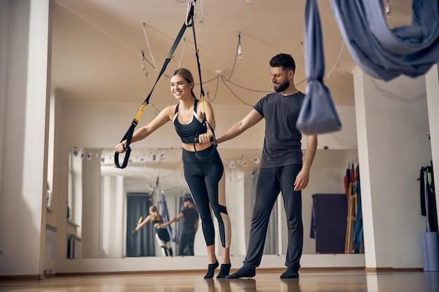 Souriante jeune femme mignonne travaillant sur un entraîneur de suspension assistée par son instructeur de fitness