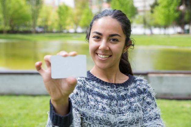 Souriante jeune femme montrant une carte de visite vierge dans le parc de la ville
