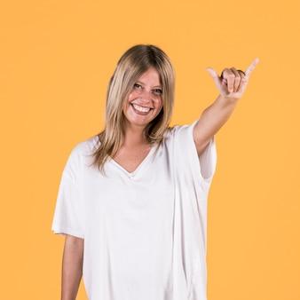 Souriante jeune femme montrant la lettre y sur fond coloré