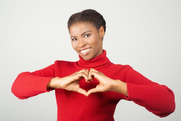 Souriante jeune femme montrant le signe de l'amour