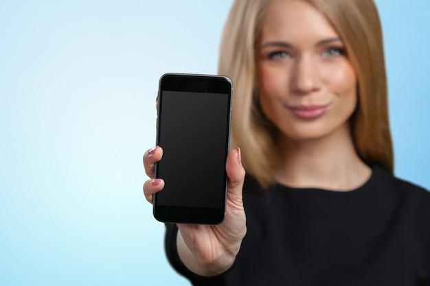 Souriante jeune femme montrant un smartphone vide