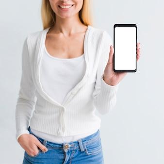 Souriante jeune femme montrant un smartphone