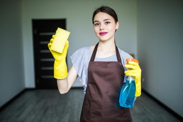 Souriante jeune femme nettoyer la fenêtre avec un chiffon
