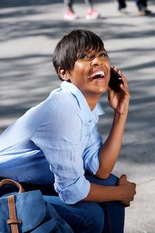 Souriante jeune femme noire assis à l'extérieur et parler au téléphone cellulaire