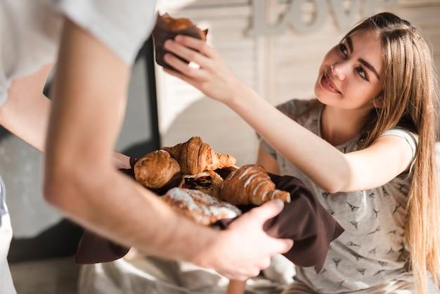 Souriante jeune femme offrant une coupe de gâteau à son petit ami tenant un plateau de croissant