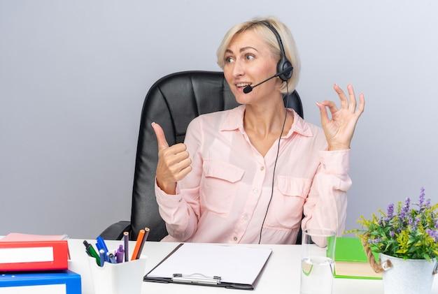 Souriante jeune femme opératrice de centre d'appels portant un casque assis à table avec des outils de bureau montrant un geste correct son pouce vers le haut isolé sur un mur blanc