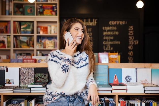 Souriante jeune femme parlant au téléphone mobile et regardant loin dans la bibliothèque