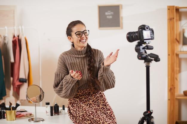 Souriante jeune femme parlant à la caméra dans beauty studio