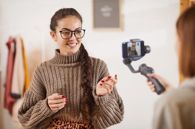 Souriante jeune femme parlant à la caméra