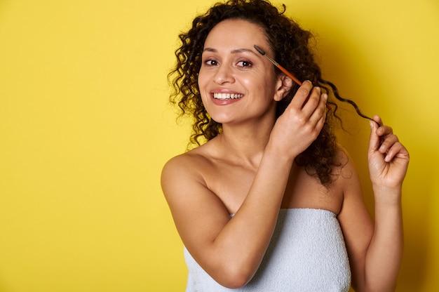 Souriante jeune femme avec une peau parfaite et un maquillage posant avec un pinceau de maquillage sur fond jaune