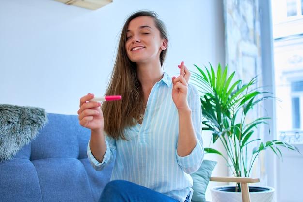 Souriante jeune femme pleine d'espoir avec deux doigts croisés espère tomber enceinte et tient en mains un test de grossesse