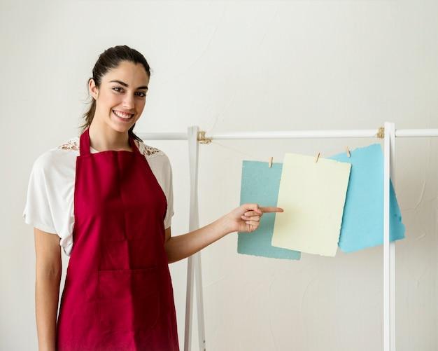 Souriante jeune femme pointant à accrocher des papiers à la main