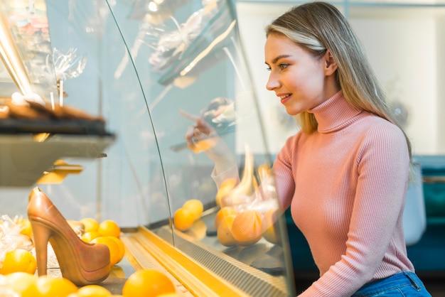Souriante jeune femme pointant sur un gâteau dans une vitrine