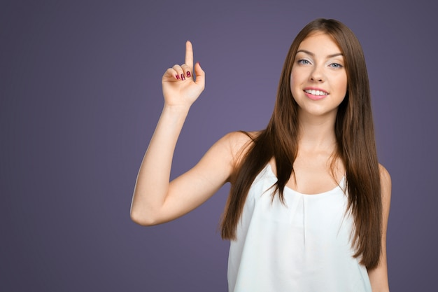 Souriante jeune femme pointant