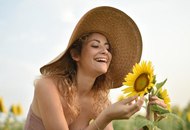 Souriante jeune femme portant un chapeau dans le champ de tournesol