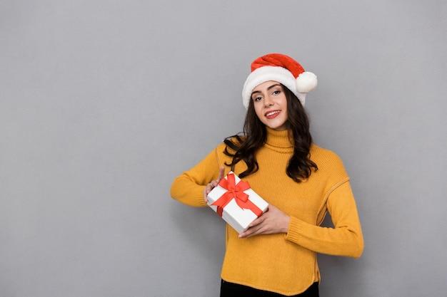 Souriante jeune femme portant un chapeau de noël debout isolé sur fond gris, tenant présent fort