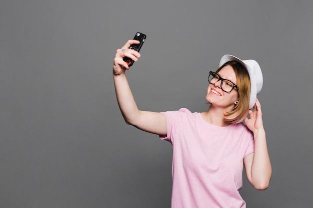 Souriante jeune femme portant chapeau prenant selfie sur téléphone portable dans un contexte gris