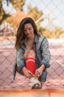 Souriante jeune femme portant des lunettes attachant la dentelle de patins à roulettes en face de maille