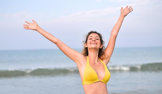 Souriante jeune femme portant un maillot de bain sur la plage - le concept de bonheur