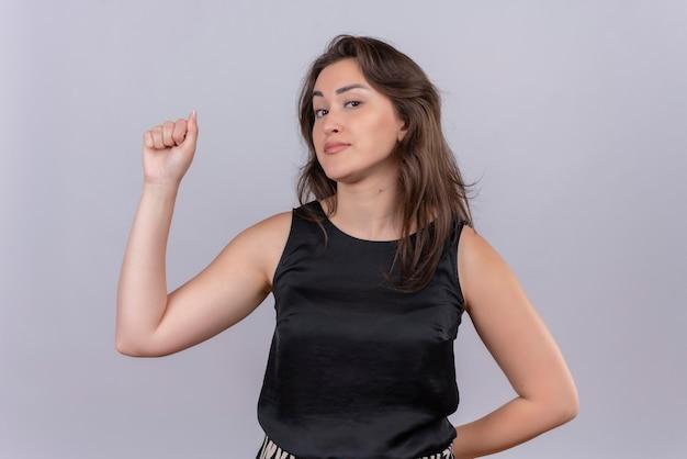 Souriante jeune femme portant un maillot noir poing levé avec une main et un autre jeu de mots sur le dos sur le mur blanc