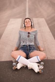 Souriante jeune femme portant des patins à roulettes assis sur la route, écoute de la musique sur un casque