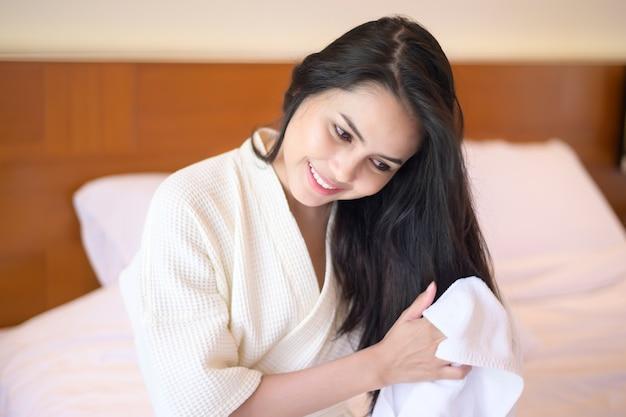 Souriante jeune femme portant un peignoir blanc en essuyant ses cheveux avec une serviette après une douche dans la chambre