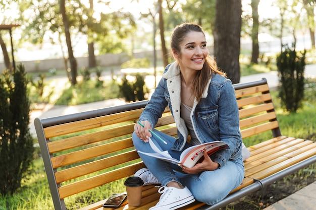 Souriante jeune femme portant une veste assise sur un banc dans le parc, lisant un magazine
