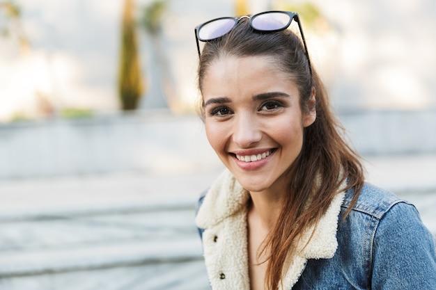 Souriante jeune femme portant une veste assise sur un banc à l'extérieur, prenant un selfie