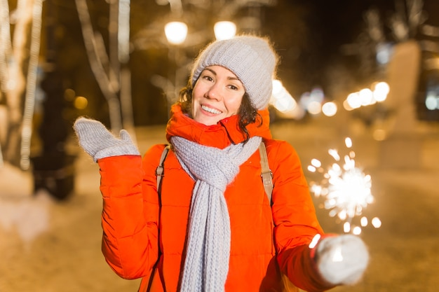 Souriante jeune femme portant des vêtements tricotés d'hiver tenant un cierge magique à l'extérieur sur fond de neige. vacances de noël.