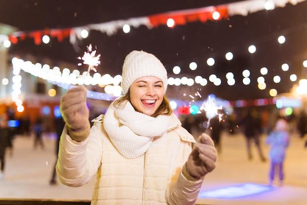 Souriante jeune femme portant des vêtements tricotés d'hiver tenant un cierge magique à l'extérieur sur fond de neige