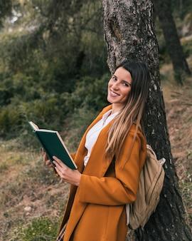 Souriante jeune femme posant sous l'arbre avec un livre à la main