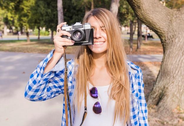 Souriante jeune femme prenant une photo sur l'appareil photo à l'extérieur