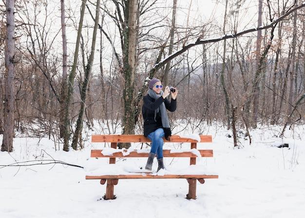 Souriante jeune femme prenant des photos en hiver assis sur un banc dans la neige