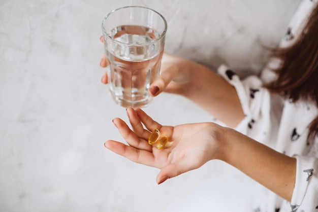 Souriante jeune femme prenant la pilule d'huile de foie de morue avec de l'eau