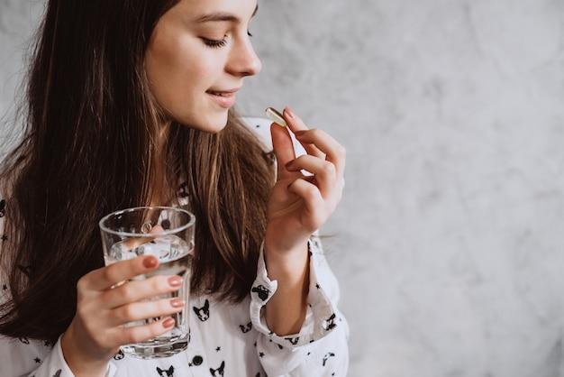Souriante jeune femme prenant des pilules avec de l'eau