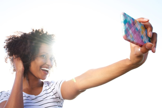 Souriante jeune femme prenant selfie avec un téléphone intelligent à l'extérieur contre le soleil