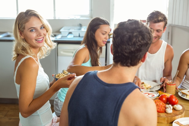 Souriante jeune femme prenant son petit déjeuner avec des amis à la maison