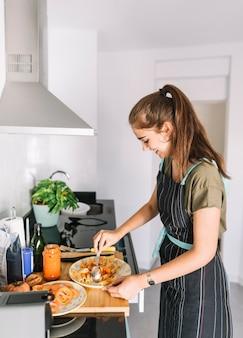 Souriante jeune femme préparant des pâtes rigatoni dans la cuisine