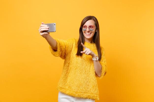 Souriante jeune femme en pull, lunettes de coeur faisant prise de selfie sur téléphone portable pointant l'index isolé sur fond jaune vif. les gens émotions sincères, mode de vie. espace publicitaire.
