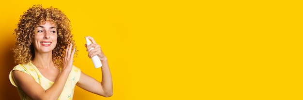 Souriante jeune femme pulvérise avec spray sur fond jaune. coiffure.