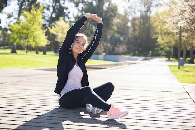 Souriante jeune femme qui s'étend de corps dans le parc de la ville