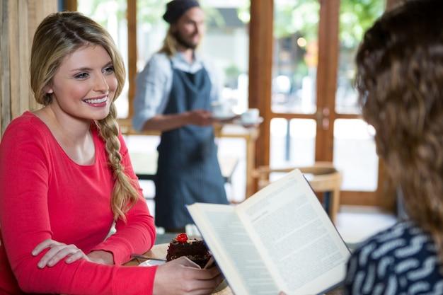 Souriante jeune femme regardant une amie dans un café