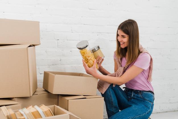 Souriante jeune femme regardant des bouteilles de collation extraites de la boîte en carton