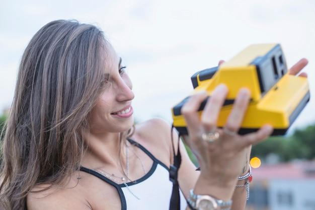 Souriante jeune femme regardant caméra instantanée en tenant dans les mains