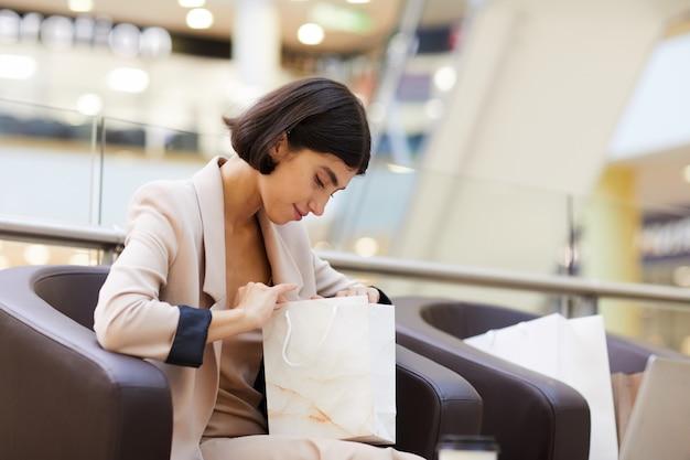 Souriante jeune femme regardant dans le sac à provisions