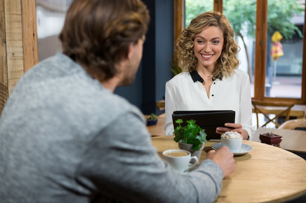 Souriante jeune femme regardant l'homme à table dans un café