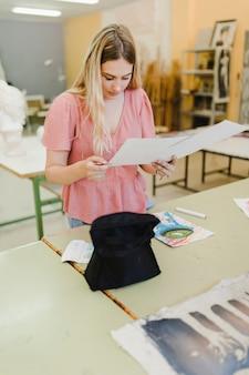 Souriante jeune femme regardant des peintures dans l'atelier